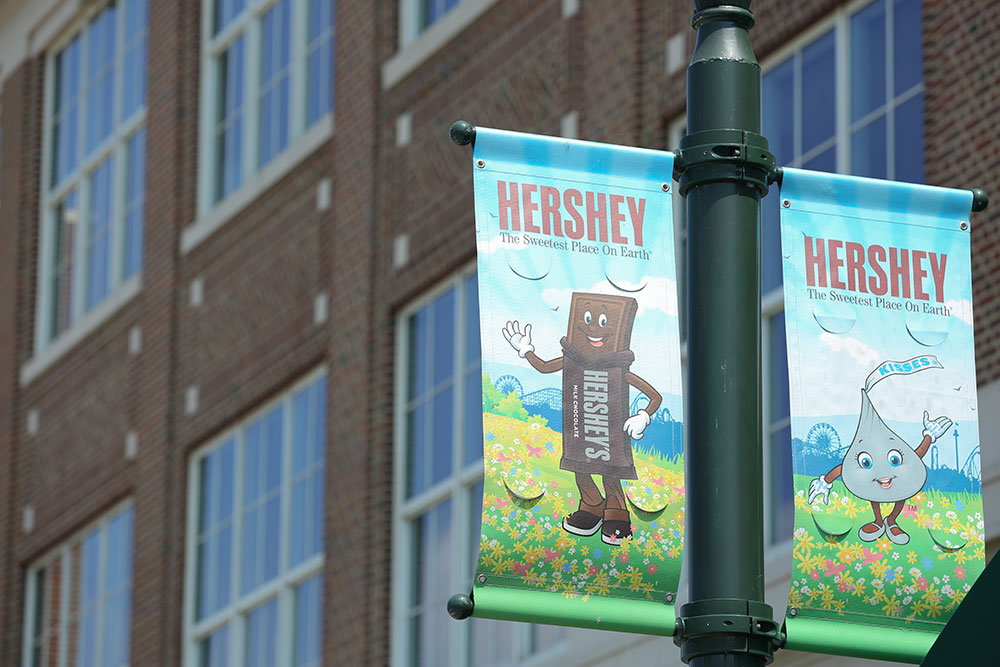Penn State College of Medicine is in Hershey, PA, a town known as the home of the HersheyPark amusement park and the Hershey Chocolate Factory. Two banners depicting cartoon candy characters are seen on a light pole in downtown Hershey, PA, in summer 2016, with a brick building with large glass windows in the background.