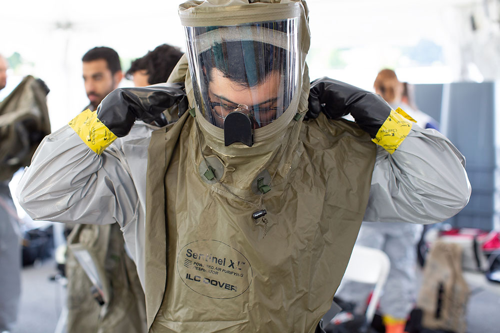 Trainees in the Emergency Medical Services Fellowship at Penn State Health participate in a mock decontamination exercise. A trainee is pictured wearing a hazmat suit.