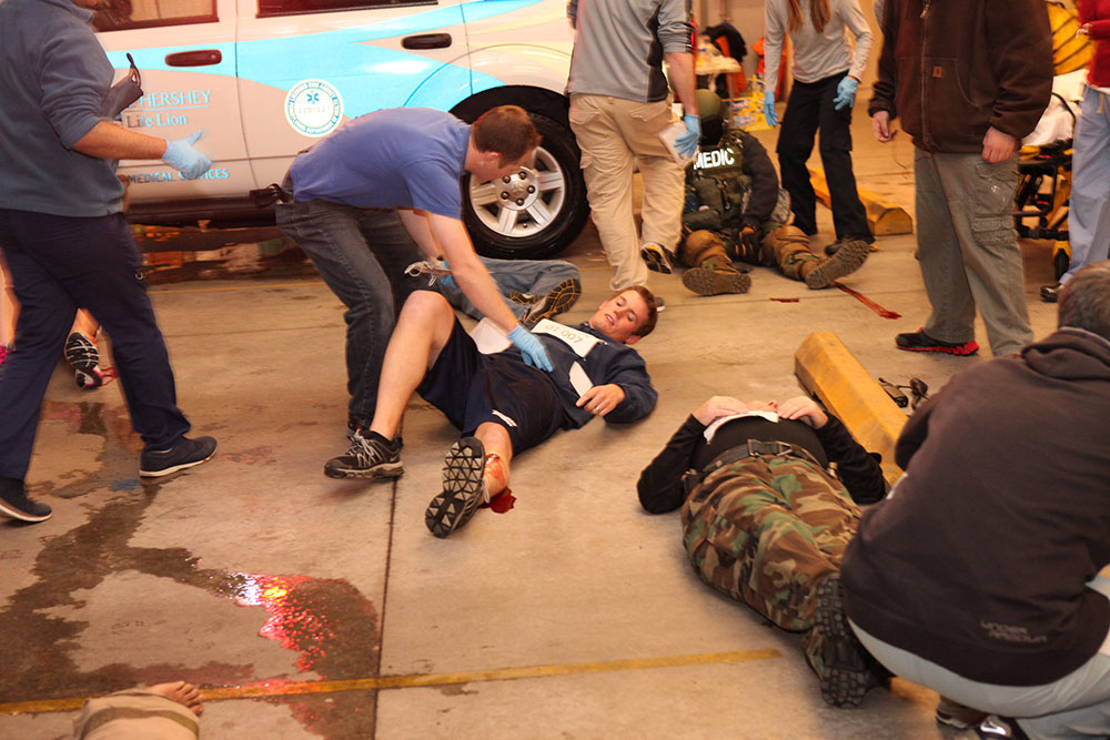 Penn State College of Medicine EMS Fellowship trainees are seen participating in a mock motor vehicle accident training exercise. Several simulated patients are seen on the ground with trainees around them.