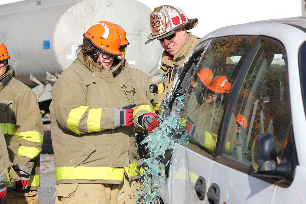 Penn State College of Medicine EMS Fellowship trainees are seen participating in a mock motor vehicle accident training exercise. Two people in firefighter-type gear are seen standing by a wrecked vehicle.
