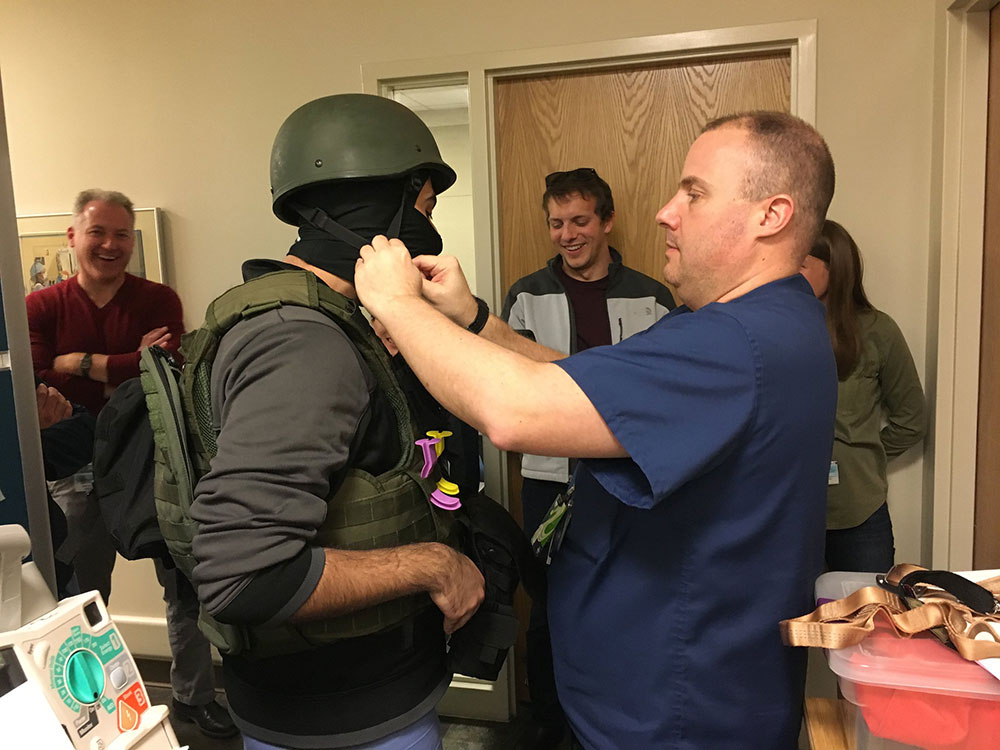 Penn State College of Medicine EMS Fellowship trainees are seen participating in a training activity. One man is seen fastening a protective helmet on another man.