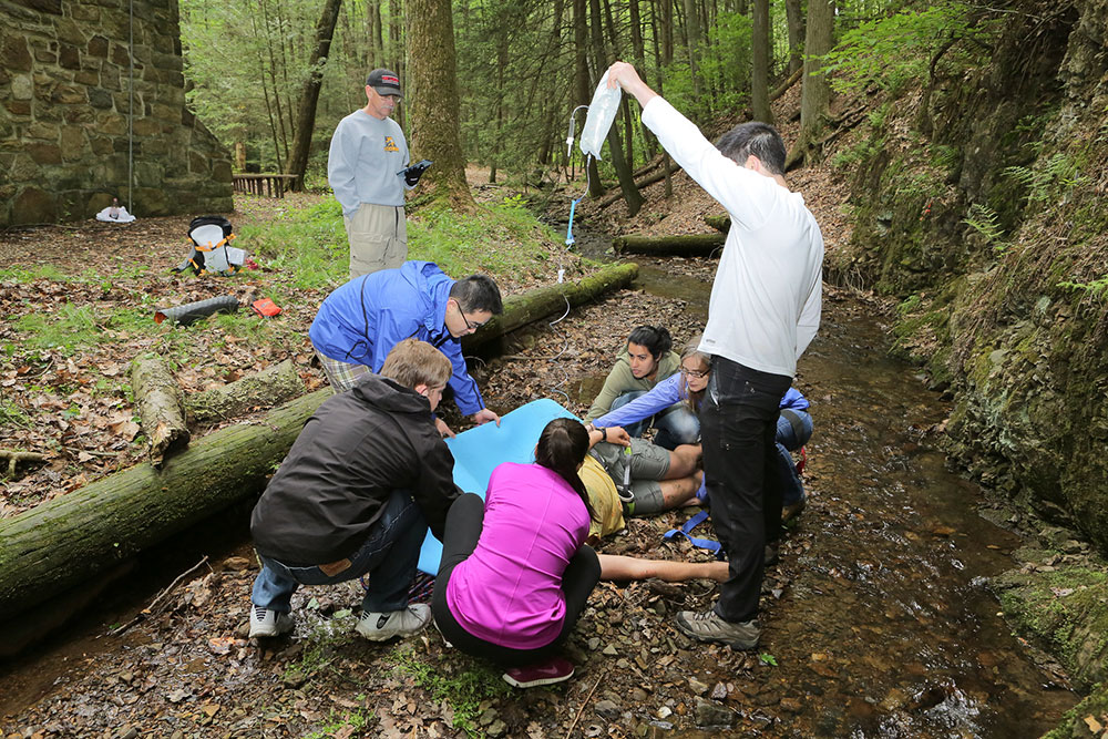 Penn State College of Medicine EMS Fellowship trainees are seen participating in a mock wilderness medicine training exercise. Trainees are seen standing in the woods, working on a simulated patient.