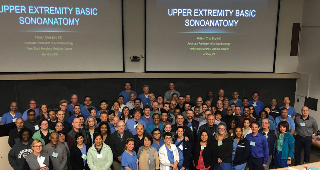 A group of faculty and participants in the Ninth Annual Ultrasound-Guided Cadaver Course for Regional Anesthesia and Point-of-Care Ultrasound is seen in a May 2019 photo. Dozens of people are standing in the front of a large lecture hall.