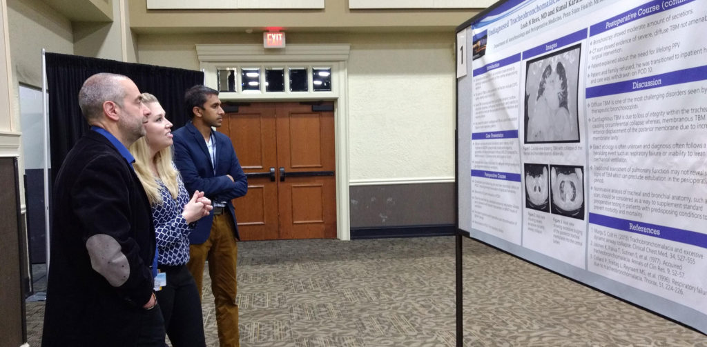 Faculty and trainees look at a poster at Penn State College of Medicine's 2019 Resident and Fellow Research Day.
