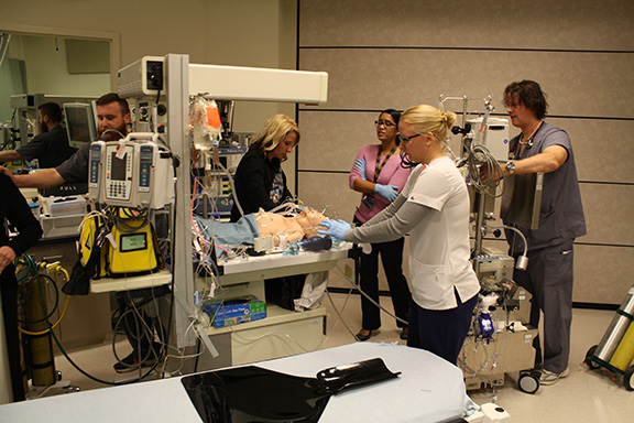 A group of people are seen in a simulated medical room.