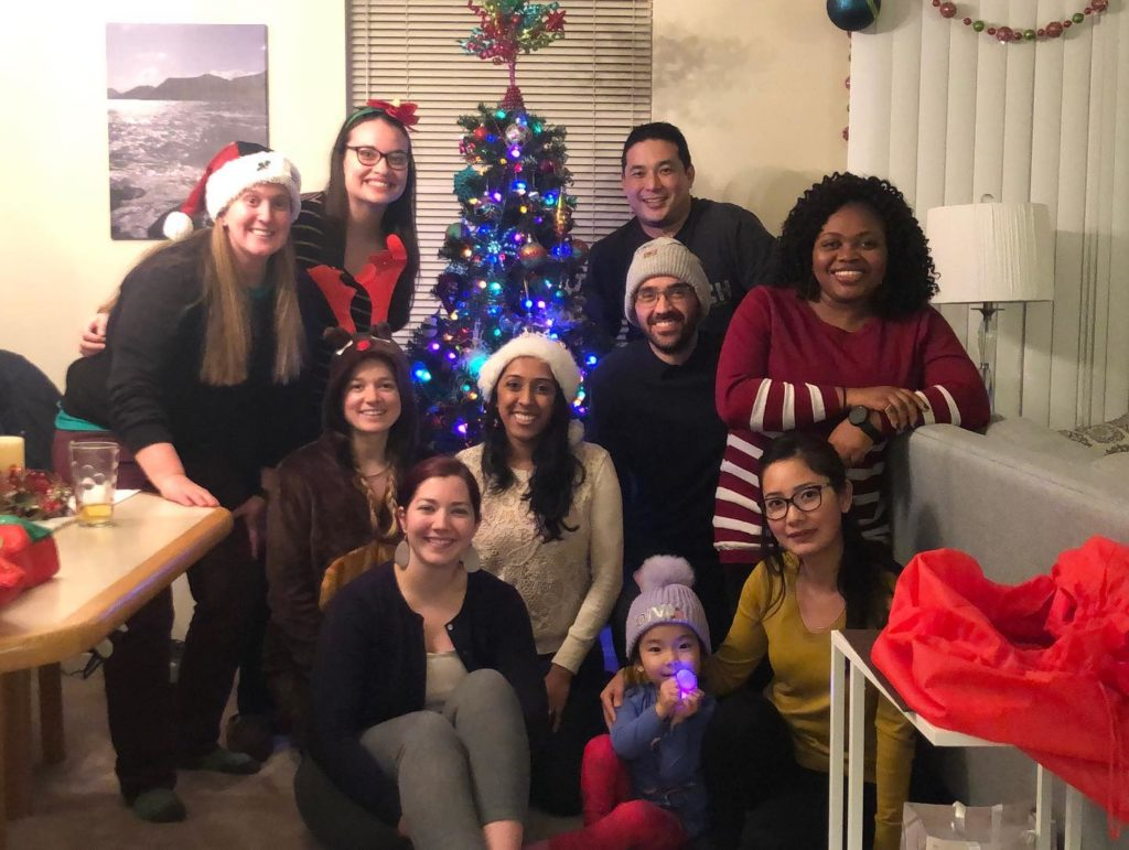 A group of approximately 10 people are seen gathered around a Christmas tree.