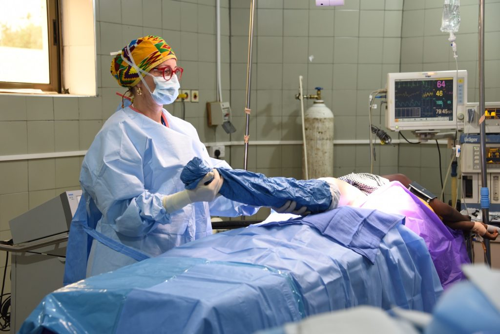 A woman wearing surgical garb stands over a patient who is laying on an operating table. The patient's face is not visible.