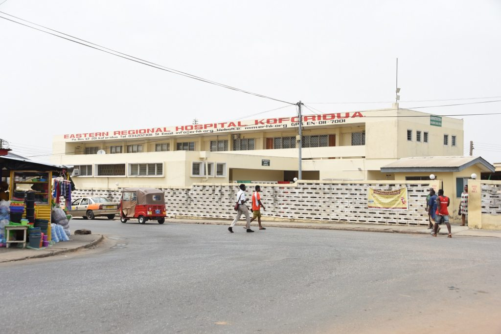 The outside of a cinderblock hospital building is seen in Ghana. The hospital's name is in large letters and people arewalking nearby.
