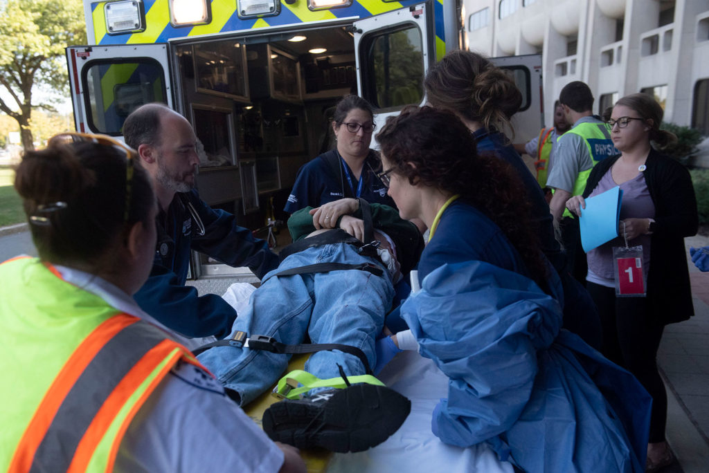 Penn State Health Milton S. Hershey Medical Center's Emergency Department participates in a full-scale exercise on Thursday, Sept. 19, 2019. Program faculty member Jeffrey Lubin, MD, at left, isseen helping to load a stretcher into an ambulance as other people look on.