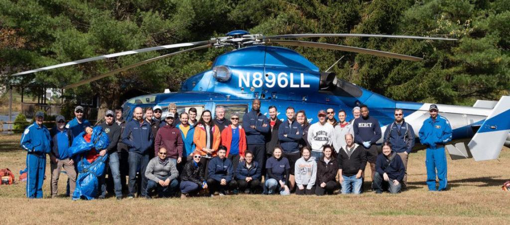 EMS Fellowship personnel are seen in front of a Life Lion helicopter in a field during a 2019 EMS Wilderness Day event.