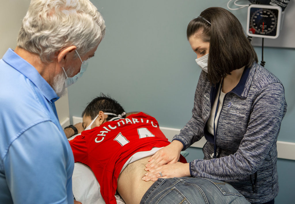A resident physician is seen pressing on the back of a patient who is lying on his stomach. A doctor looks on.