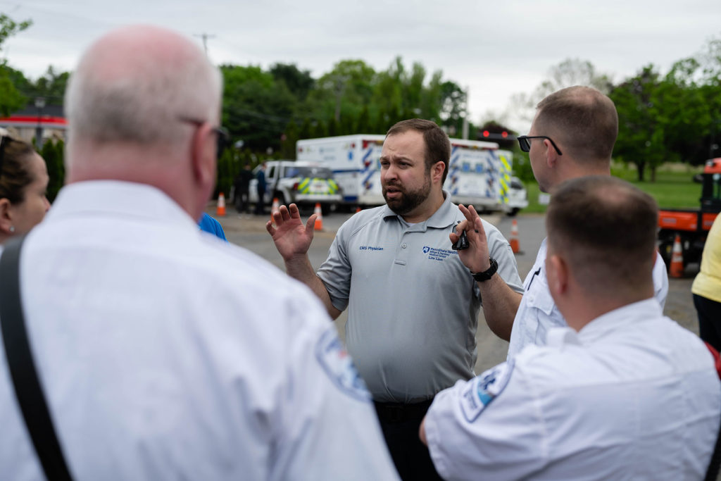 Joshua Knapp, a 2019 graduate of the Emergency Medical Services Fellowship, is pictured instructing a group of people whose faces are not visible during a 2019 activity. Ambulances are visible in the background.