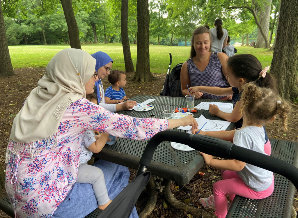A group of people from diverse backgrounds sits around an outdoor table.