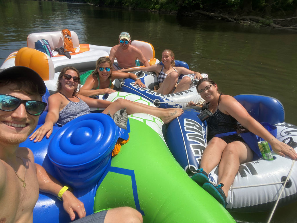 A group of six people are seen sitting in several different rafts on a creek in 2019.