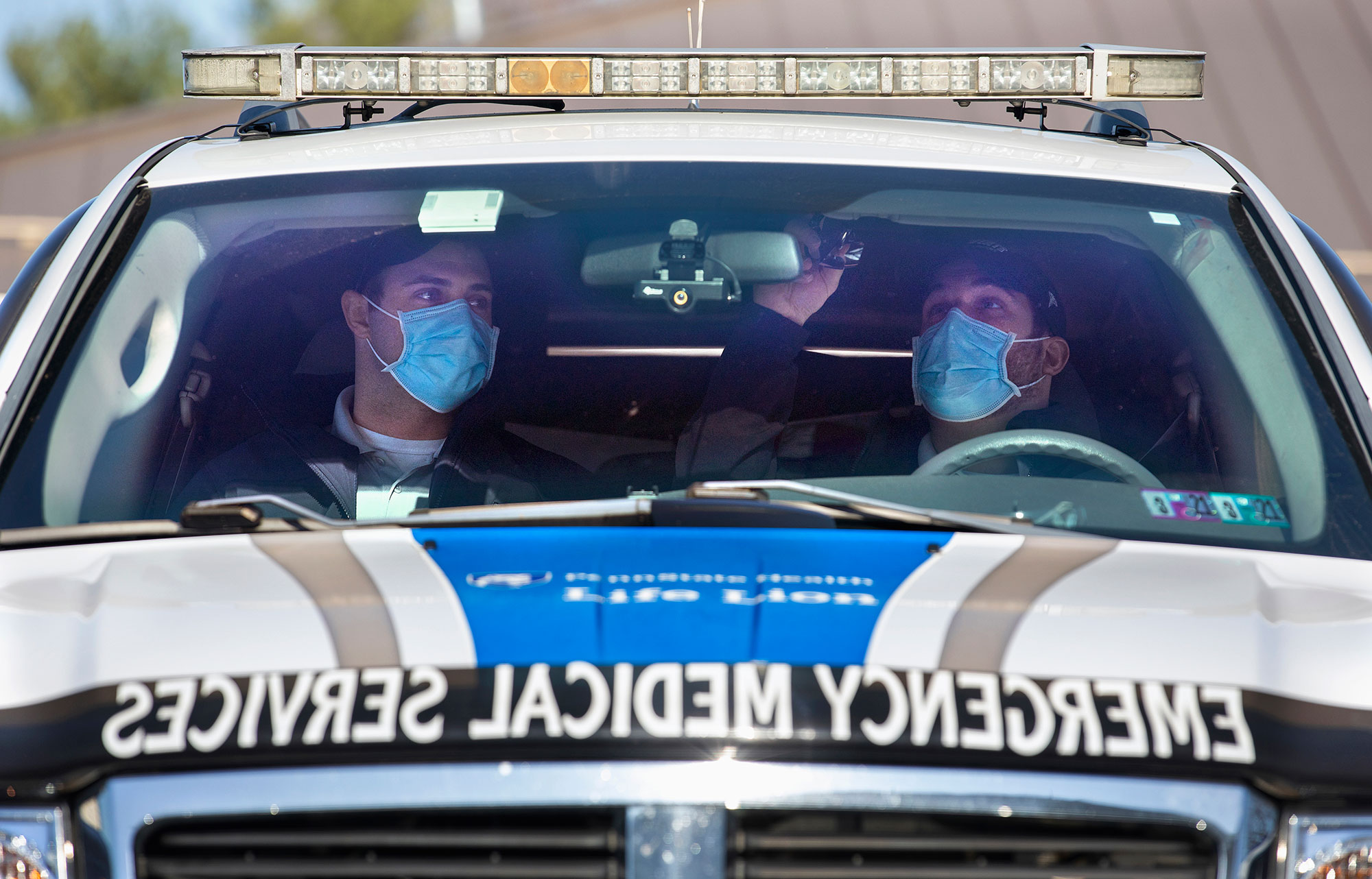 Penn State College of Medicine EMS Fellowship trainees, both wearing masks, are seen in the front seat of an EMS vehicle.