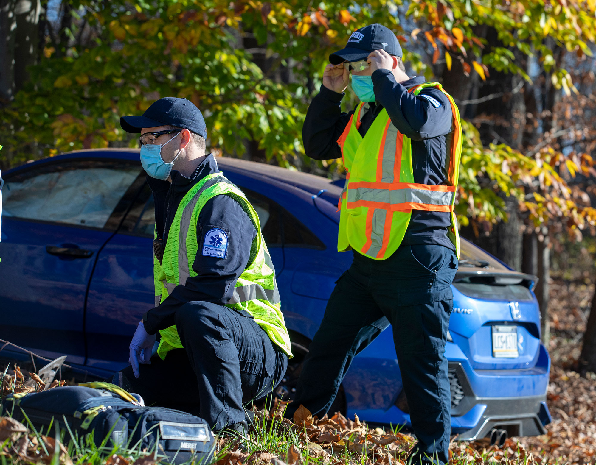 Penn State College of Medicine EMS Fellowship trainees are seen participating in a mock training exercise. One trainee is kneeling and one is standing in front of a blue car with trees in the background.