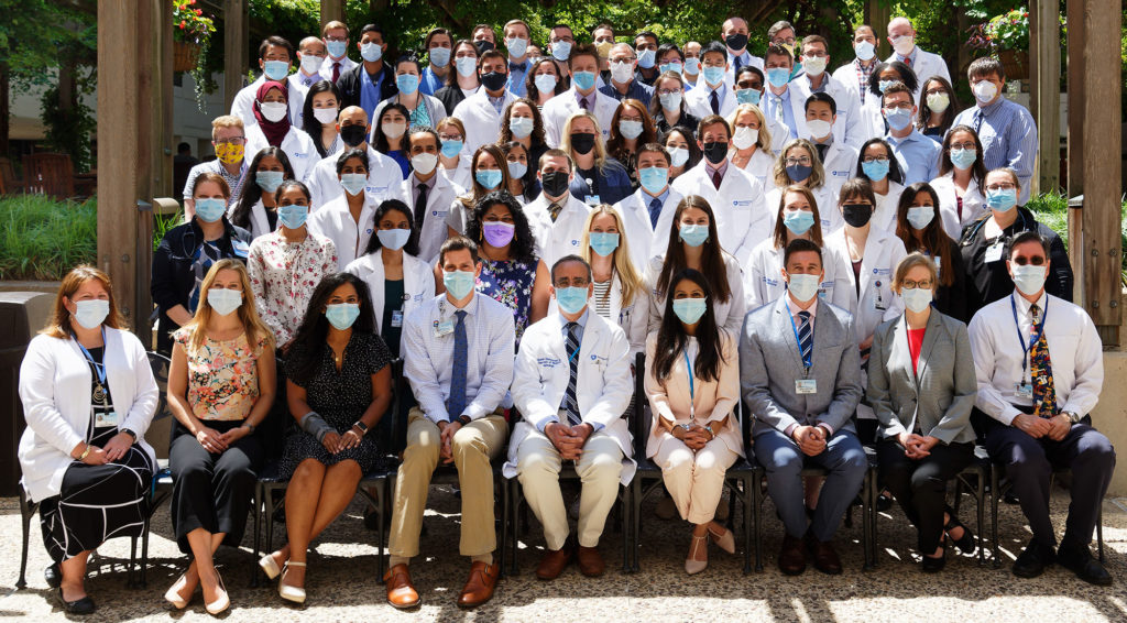 40 to 50 people wearing facemasks are seen in rows in an outdoor courtyard. They are the members of the Internal Medicine Residency at Penn State Health Milton S. Hershey Medical Center.